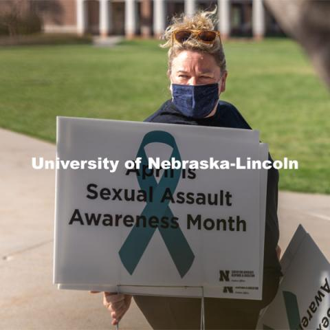 CARE Advocate Melissa Wilkerson organizes signs before placing them at the Nebraska Union Greenspace. Flags and signs are placed in the Nebraska Union Greenspace to promote Sexual Assault Awareness Month. April 4, 2021. Photo by Jordan Opp for University Communication.