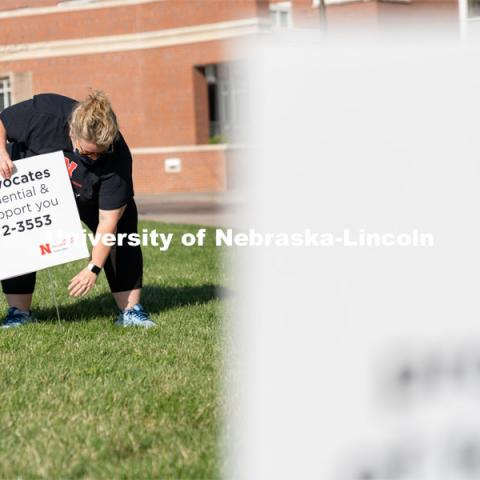 CARE Advocate Melissa Wilkerson places a sign at the Nebraska Union Greenspace. Flags and signs are placed in the Nebraska Union Greenspace to promote Sexual Assault Awareness Month. April 4, 2021. Photo by Jordan Opp for University Communication.