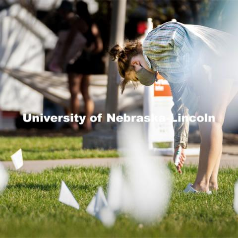 Sophomore psychology major Violet Hudson places flags across the Nebraska Union Greenspace. Flags and signs are placed in the Nebraska Union Greenspace to promote Sexual Assault Awareness Month. April 4, 2021. Photo by Jordan Opp for University Communication.
