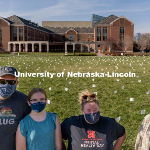 Left to right: Matt Milner, McClellan Milner, Melissa Wilkerson and Violet Hudson pose for a portrait in front of their display at the Nebraska Union Greenspace. Flags and signs are placed in the Nebraska Union Greenspace to promote Sexual Assault Awareness Month. April 4, 2021. Photo by Jordan Opp for University Communication.