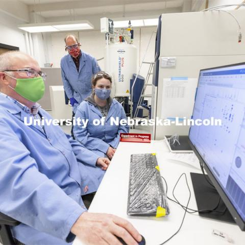 Dan Draney, Pat Dussault, and Michelle Takacs look over results from the Research Instrumentation Facility's high-field NMR (nuclear magnetic resonance) spectrometer in Hamilton Hall. April 6, 2021. Photo by Craig Chandler / University Communication.