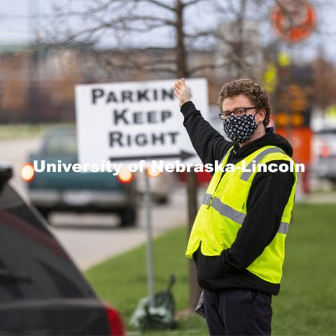 Noah Schwendeman, Student Support Specialist with Husker Hub, directs traffic along Pinnacle Arena Drive as people arrive for their vaccine. More than 150 UNL faculty, staff and student volunteers are helping at the COVID vaccine clinic at Pinnacle Bank Arena this week. April 7, 2021. Photo by Craig Chandler / University Communication.